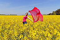 Woman standing in rape field holding blowing red cloth - KLRF000461