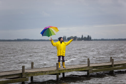 Germany, Steinhuder Meer, woman wearing yellow rain coat and Wellington boots standing on jetty - KLRF000464