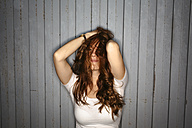 Redheaded young woman with dishevelled hair - GIOF001387