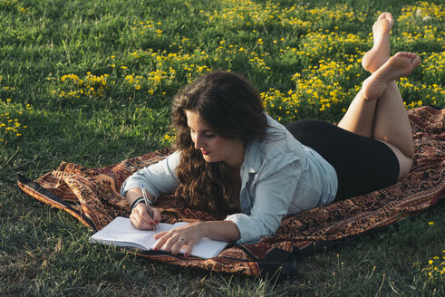 Young woman lying on blanket on a meadow writing down something in her diary - SKCF000160
