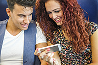 Smiling young couple looking at cell phone - SIPF000767