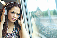 Portrait of relaxed young woman in a train listening music with headphones - SIPF000770