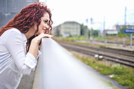 Redheaded young woman leaning on railing looking at distance - SIPF000776