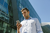 Portrait of businessman looking at cell phone - BOYF000509