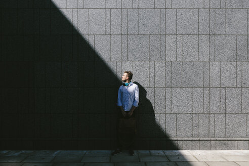Young businessman standing in front of a grey wall looking up - BOYF000518