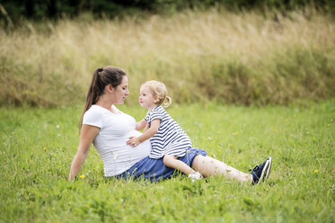 Pregnant woman sitting in grass with little daughter touching mother's belly - HAPF000719