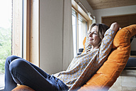 Smiling woman relaxing in armchair - RBF004841