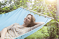 Smiling woman relaxing in hammock - RBF004847