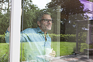 Mature man holding cup looking out of window - RBF004853