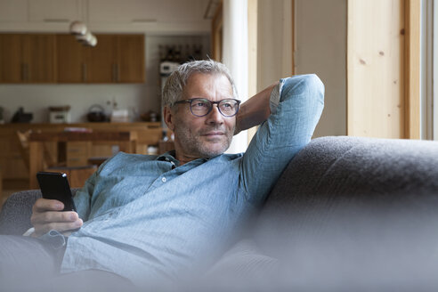 Mature man holding cell phone sitting on couch - RBF004856