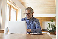 Mature man using laptop on table at home - RBF004862