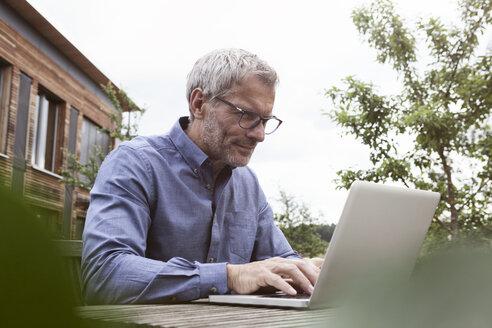 Mature man using laptop on garden table - RBF004871