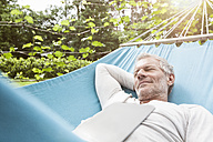 Mature man sleeping in hammock with digital tablet on his chest - RBF004874