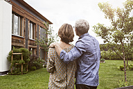 Mature couple in garden looking at house - RBF004877