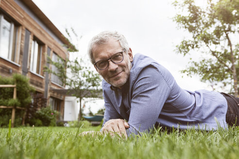 Portrait of smiling mature man lying in garden - RBF004880