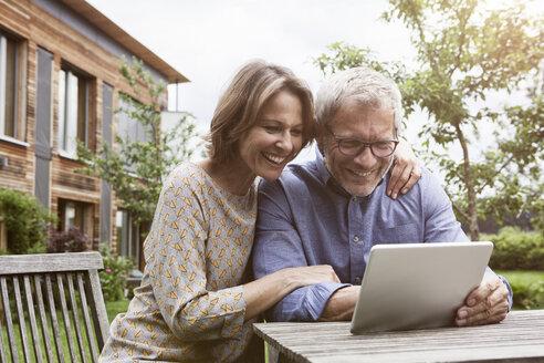 Happy mature couple sharing digital tablet in garden - RBF004883