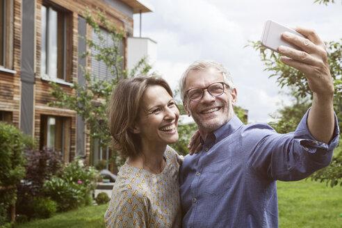 Happy mature couple taking selfie in garden - RBF004886