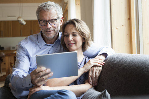 Mature couple sharing digital tablet on couch - RBF004892