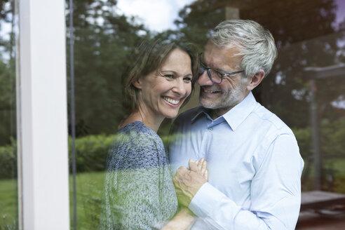 Happy mature couple behind windowpane - RBF004895