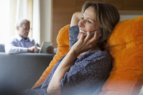 Smiling woman at home on cell phone with husband in background - RBF004901