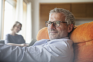 Man relaxing in armchair with wife in background - RBF004904