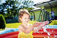 Little girl having fun in paddling pool in the garden - HAPF000755