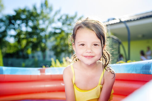 Portrait of smiling little girl sitting in paddling pool - HAPF000758