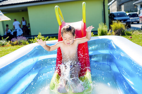 Little boy sliding into paddling pool - HAPF000761