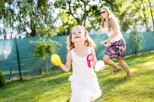 Little girl having fun with water bombs in the garden - HAPF000764