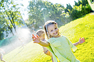Little girl having fun with lawn sprinkler in the garden - HAPF000767
