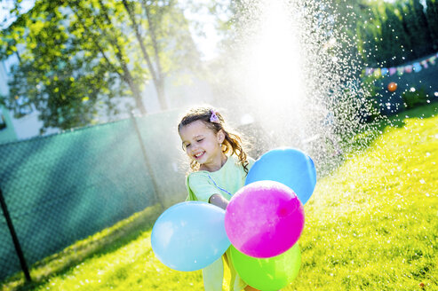 Little girl with balloons having fun with lawn sprinkler in the garden - HAPF000770