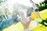 Little boy with balloons having fun with lawn sprinkler in the garden - HAPF000773