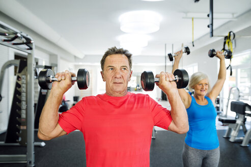Senior man and mature woman working out in fitness gym - HAPF000776