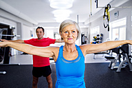 Mature woman and senior man doing gymnastics in fitness gym - HAPF000785