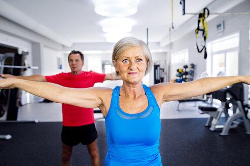Mature woman and senior man doing gymnastics in fitness gym - HAPF000785