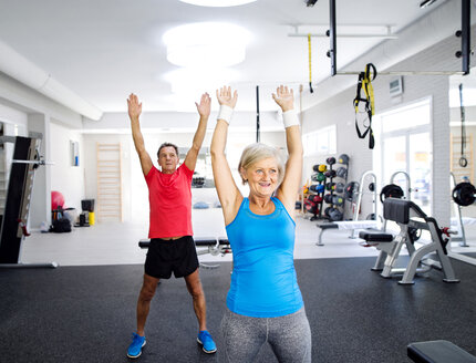 Mature woman and senior man doing gymnastics in fitness gym - HAPF000788