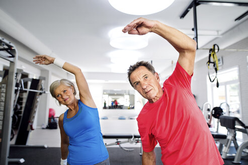 Mature woman and senior man doing gymnastics in fitness gym - HAPF000791