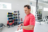 Senior man in fitness gym looking at smartwatch - HAPF000836