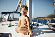 Little boy sitting on bow of a sailing boat at sunlight - JRFF000830