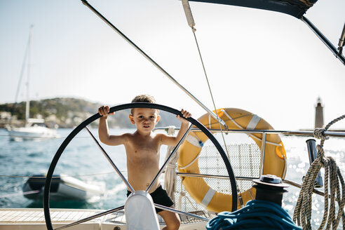 Little boy at the helm of a sailing boat - JRFF000833