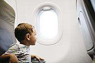 Little boy looking out of window while flying on an airplane - JRFF000836