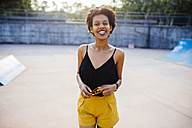Portrait of smiling young woman in a skatepark - GIOF001403