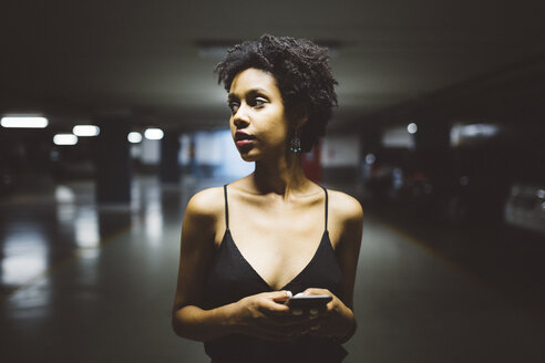Young woman with smartphone in a car park - GIOF001415