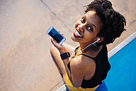 Smiling young woman with earphones and cell phone sitting in a skatepark looking up to camera - GIOF001418