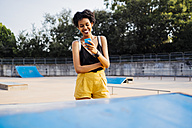 Smiling young woman in a skatepark looking at cell phone - GIOF001430