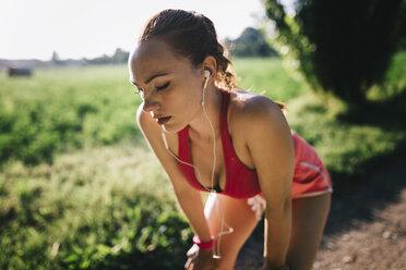 Italy, Tuscany, sportswoman, headphones, break - GIOF001451