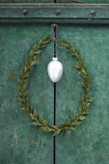 Silver Easter egg and box tree wreath hanging in front of green door - ASF005976