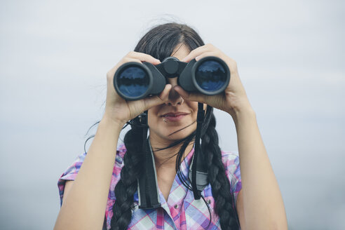 Woman looking through binocular - DAPF000253