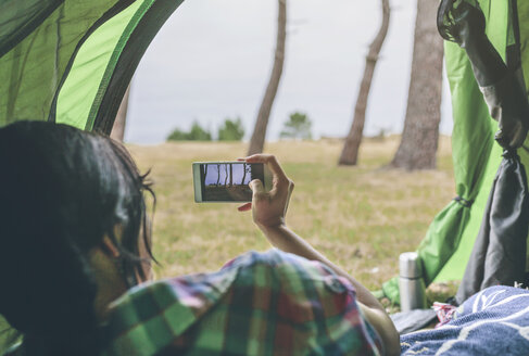 Back view of young woman with smartphone lying in a tent taking pictue from outside - DAPF000259