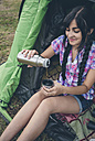 Young woman sitting in a tent pouring coffee from thermos flask into cup, partial view - DAPF000262